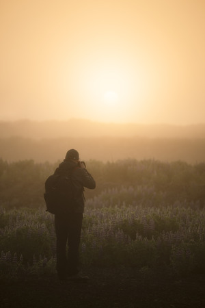 Tourist photographer contemplates and photographs a misty sunrise in Iceland. Beautiful light of the sun through the fog