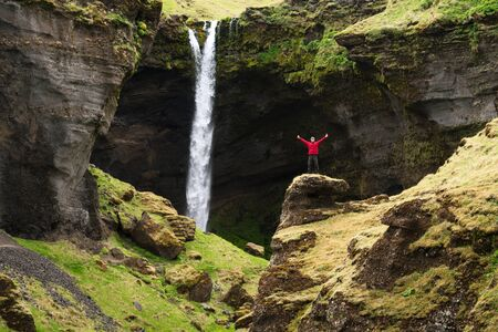 Kvernufoss waterfall in Iceland. Tourist in a red jacket inspects sight