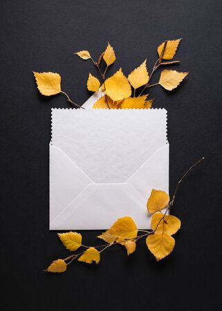 Envelope with a congratulation on a black background. Autumn card with fall foliage