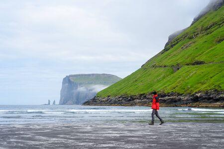 View of Risin og Kellingin (Risin and Kellingin) cliffs from the beach of Tjornuvik village. Streymoy Island, Faroe islands. A tourist in a red jacket walks along the beach at low tide
