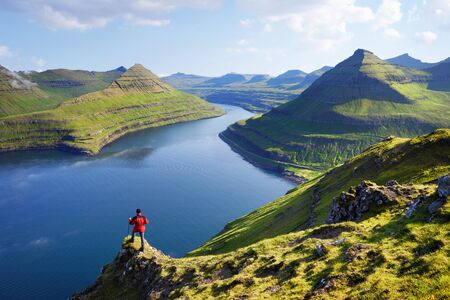 View on Funningur fjord from the Funningur top. Eysturoy Island, Faroe islands. Tourist in a red jacket explores natural attractions. Summer mountain landscape Stok Fotoğraf