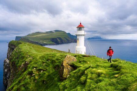 Mykinesholm islet lighthouse near Mykines island. Mykinesholmur, Faroe islands. Tourist in red jacket explores attractions. Summer landscape