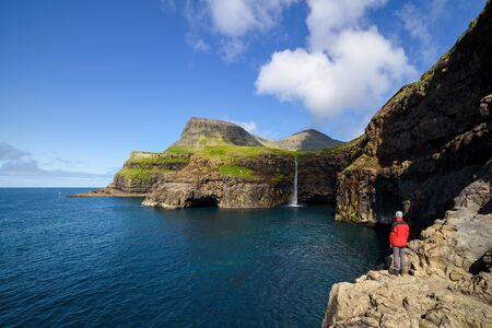 Mulafossur waterfall in Gasadalur. Vagar Island, Faroe islands. Summer landscape overlooking the cape in the Atlantic Ocean. Tourist in a red jacket explores natural attractions