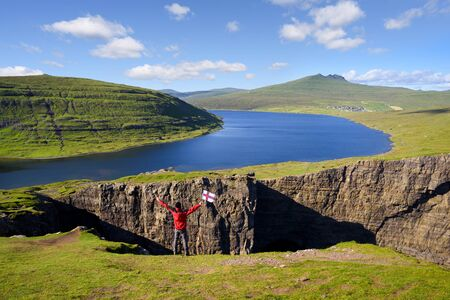 Lake Leitisvatn (Sorvagsvatn) on cliffs above the Atlantic ocean. Vagar island, Faroe Islands, Kingdom of Denmark, Europe. Tourist with flag of Faroe Islands visiting a natural landmark. Summer landscape with a beautiful view in sunny weather