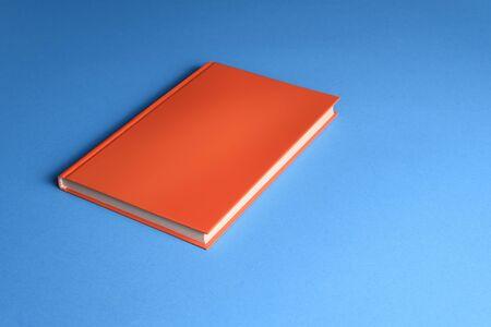 Hardcover orange book mocap on blue background