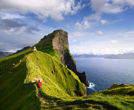 Kallur Lighthouse on Kalsoy island. Hiking on the Faroe islands. Tourist in a red jacket visiting a tourist attraction. Summer mountain landscape