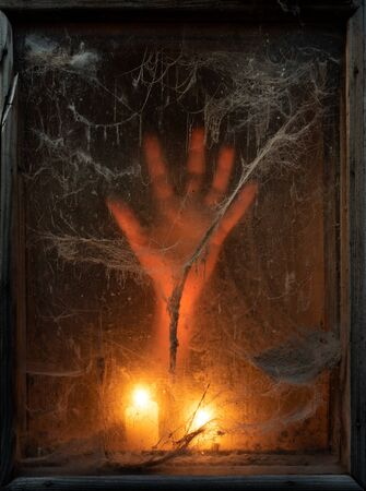 Scary halloween background with creepy old spider web (cobwebs) in a dark window. Hand in the light of candles