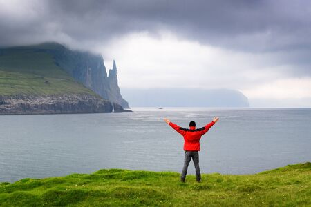 Trollkonufingur viewpoint. Vagar island, Faroe Islands. Tourist in red jacket looks at  ocean cliffs and Witches Finger Trail