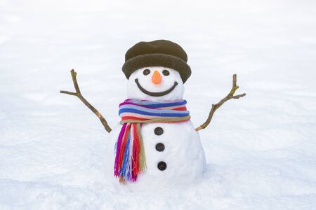 Christmas card. Funny snowman with a bright striped scarf on a background of white snow Stok Fotoğraf