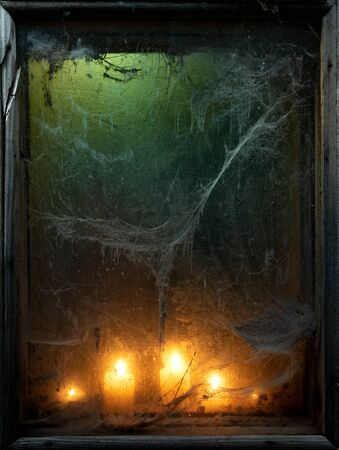 Halloween background with creepy old spider web in a scary dark window