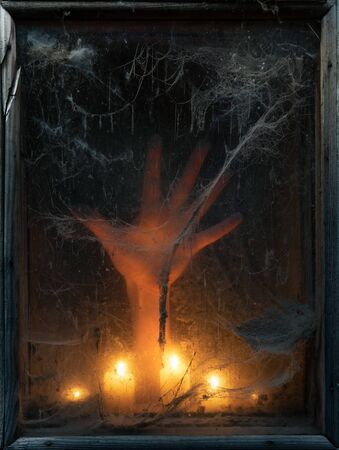 Halloween background with a scary and creepy spider web in an old window. Hand in the light of candles