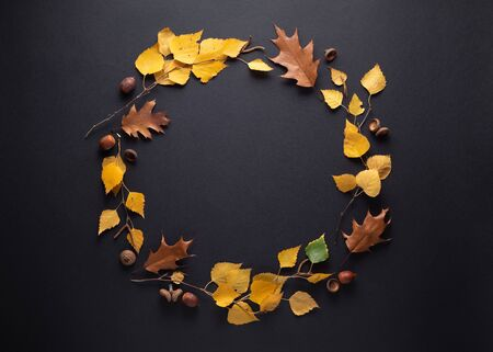 Round frame of autumn foliage on a black background with copy space for text