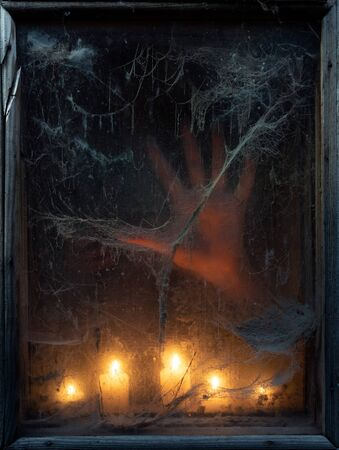 Halloween card with ghost hand in the dark. Cobweb in the old window. Scary creepy background