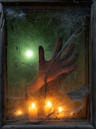 Halloween banner with spooky spider web in an old window. Background for the holiday. Hand of a ghost in the darkness in the light of candles