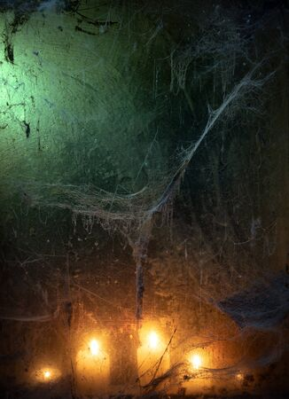 Halloween card with spider web in the dark. Candlelight in an old window. Scary creepy background