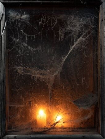 Halloween holiday. Spooky background with a scary cobweb in an old window. Candlelight in the dark Stok Fotoğraf