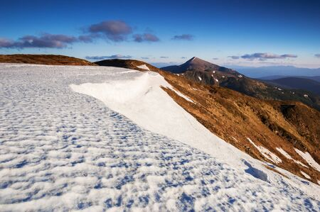 Spring thaw. Landscape with melting snow in the mountains. Sunny morning with blue sky. View of the peak of Hoverla, Ukrainian Carpathians Stok Fotoğraf