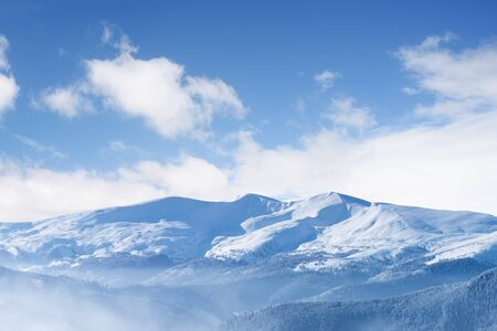 View of a mountain range with snowy peaks. Landscape with blue sky and beautiful white clouds. Sunny frosty day. Winter background for design Stok Fotoğraf