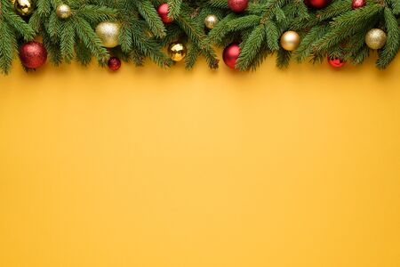 Decorative border of Christmas balls and fir branches. Yellow background for Christmas and New Year design. Copy space for promotions, advertising and congratulation text