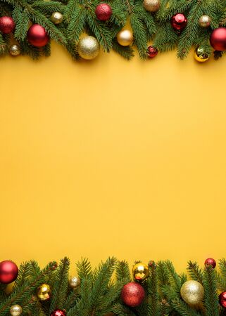 Decorative frame of fir branches and Christmas balls. Yellow background for Christmas design. Copy space for promotions, and congratulation text Stok Fotoğraf