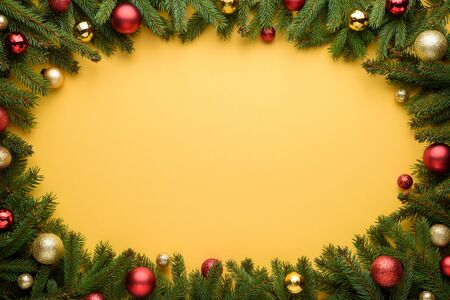 Oval frame of Christmas balls and fir branches. Yellow background for Christmas and New Year design. Copy space for promotions, advertising and congratulation text