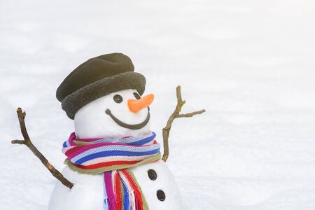 Christmas (New Year) card with a smiling snowman in a city park. White copy space to insert a greeting or festive text