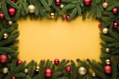 Decorative frame of Christmas balls and fir branches. Yellow background for Christmas and New Year design. Copy space for promotions, advertising and congratulation text