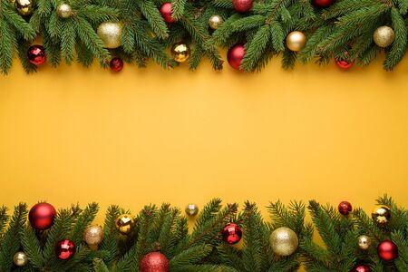 Decorative frame of Christmas balls and fir branches. Yellow background for Merry Christmas and New Year design. Copy space for promotions, and congratulation text