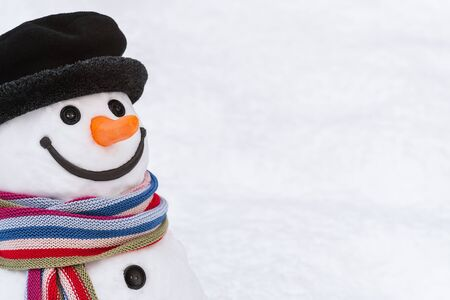 Portnet of a smiling snowman with a striped scarf and a black hat. White copy space for tex
