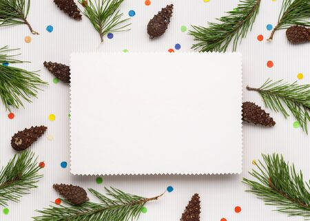 Merry Christmas and happy New Year background. White note paper sheet. Decor from pine branches, cones and festive confetti