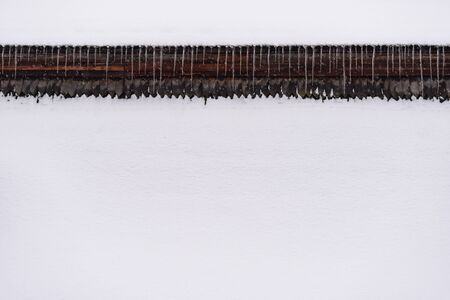 Abstract winter background with snow. Icicle border under the roof of the house