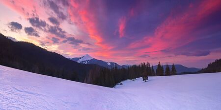 Fabulous winter landscape with a lonely wooden house in the mountains. Colorful sunset with beautiful clouds. Snowcapped mountain top