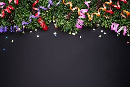 Christmas border with pine decorated branches and festive confetti on a black background. Copy space for text