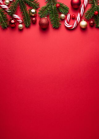 Red background. Christmas and New Year border of fir branches, Christmas balls and candy cane Stok Fotoğraf