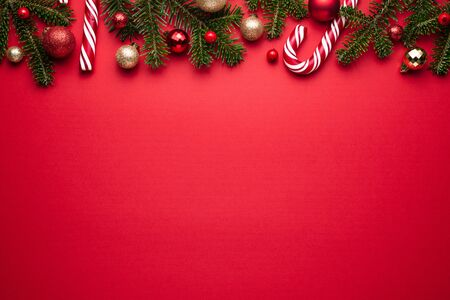 Merry Christmas and happy New Year border on red background. Festive decor of fir branches, Christmas balls and candy cane