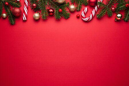 Prettige kerstdagen en gelukkig Nieuwjaar grens op rode achtergrond. Feestelijk decor van dennentakken, kerstballen en snoepriet Stockfoto