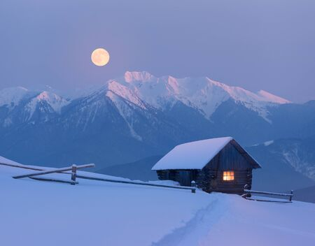 Snowy house in the mountains. Fairy night view with full moon. Winter wonderland with footsteps in snow
