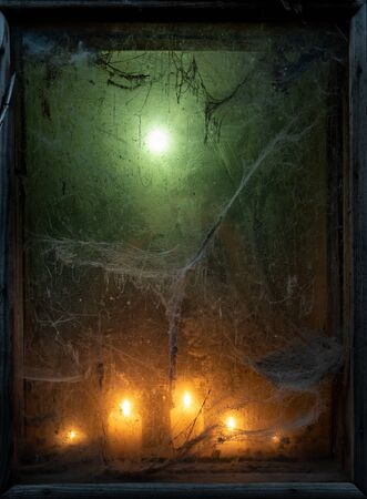 Eerie light of candles in an old window with a cobweb. Halloween background with copy space for text