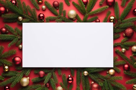 Christmas background with white note paper. Decorative festive frame of fir branches and Christmas balls
