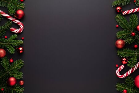 Black christmas background. Festive border frame of fir branches, red Christmas balls and candy canes Stok Fotoğraf