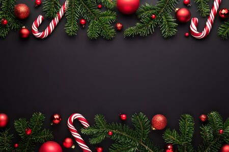 Black Christmas background. Decorative border frame of fir branches, red Christmas balls and Candy canes Stok Fotoğraf - 131868929