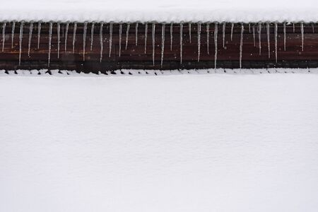 Winter snowy background with copy space. Decorative icicle border under the roof