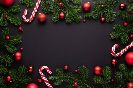 Black Christmas background. Decorative frame of fir branches, Christmas balls and Candy canes Stok Fotoğraf