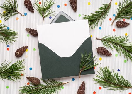 Merry Christmas and happy New Year card in envelope. White note paper sheet. Decor from pine branches, cones and festive confetti Stok Fotoğraf