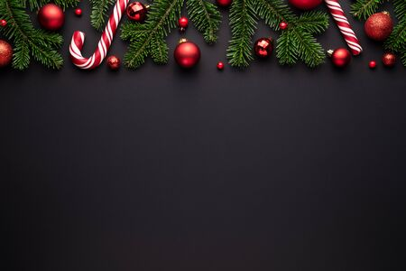 Black christmas background. Festive border of fir branches, Christmas balls and candy canes Stok Fotoğraf