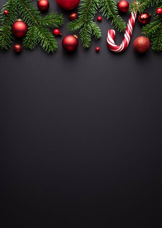 Black Christmas or New Year background. Decorative border of fir branches, red Christmas balls and Candy canes. Copy space for text Stok Fotoğraf