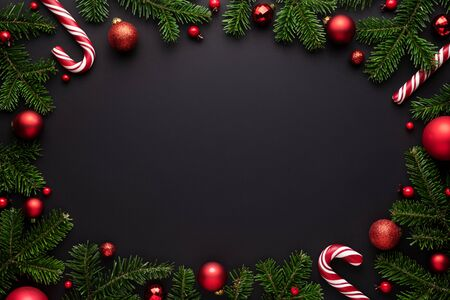 Black Christmas background. Decorative oval frame of fir branches, Christmas balls and Candy canes. Copy space for text Stok Fotoğraf - 132100265