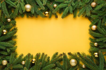 Yellow Christmas or New Year background. Decorative frame of fir branches and Christmas balls. Copy space for text Stok Fotoğraf