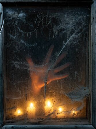 Scary Halloween Party Background. Hand of a ghost in the dark. Old spider web in the light of candles Stok Fotoğraf