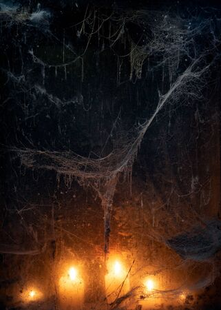 Candlelight in terrible darkness. A spooky web in an old window. Halloween Party Background Stok Fotoğraf - 132408338